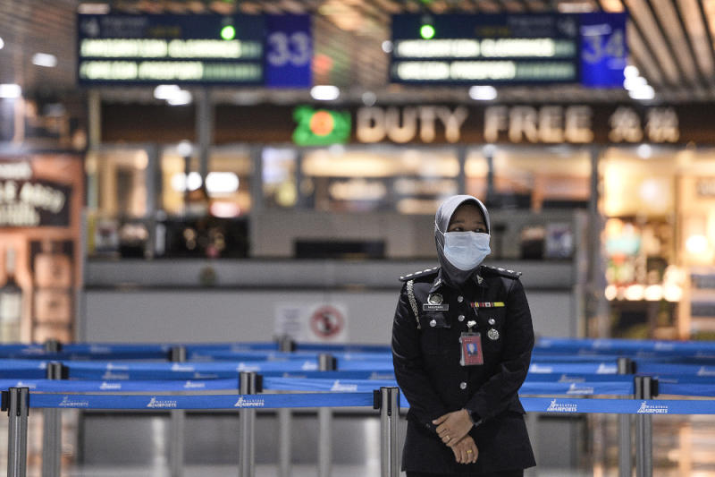 A KLIA safety officer wearing a mask is pictured at KLIA March 10, 2020. — Picture by Miera Zulyana