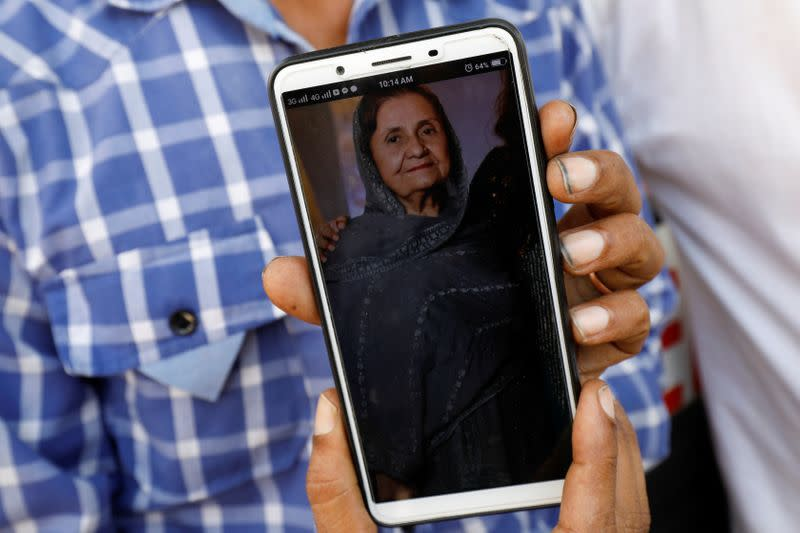 Shahid Ahmed, 45, holds his mobile phone displaying photo of his mother Irshad Begum, 72, who was killed in a plane crash, in Karachi
