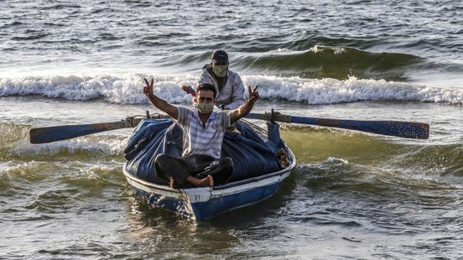 Seorang nelayan Palestina yang mengenakan masker karena pandemi virus corona COVID-19 menunjukkan isyarat kemenangan saat menangkap ikan di Laut Mediterania, Rafah, Jalur Gaza, Rabu (2/9/2020). (SAID KHATIB/AFP)