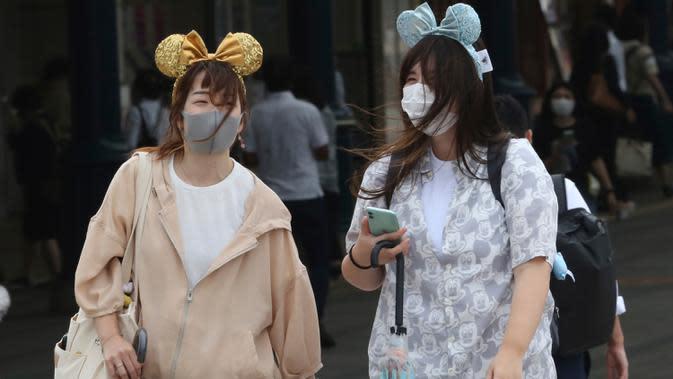 Pengunjung mengenakan masker guna melindungi diri dari virus corona berjalan menuju pintu masuk Tokyo Disneyland di Urayasu, dekat Tokyo, Rabu (1/7/2020). Tokyo Disneyland dibuka kembali untuk pertama kalinya dalam empat bulan setelah sempat ditutup karena penyebaran Covid-19. (AP/ Koji Sasahara)