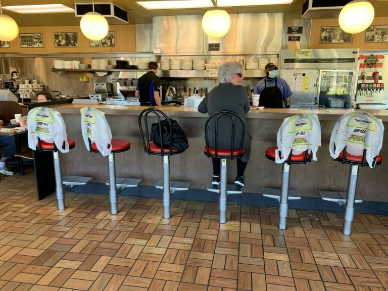 Kim Kaseta waits for her breakfast at the counter of a Waffle House in Atlanta, as Georgia relaxed its coronavirus lockdown restrictions to allow restaurants to provide limited dine-in service