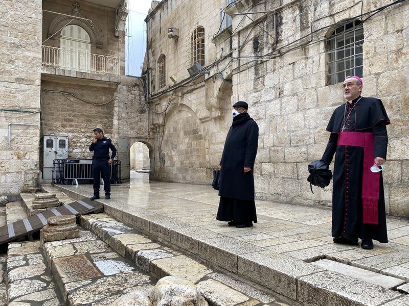 Archbishop Pierbattista Pizzaballa, apostolic administrator of the Latin Patriarchate of Jerusalem stands at the entrance to the Church of the Holy Sepulchre for the Good Friday service amid restrictions due to the coronavirus disease (COVID-19) in Jerusal