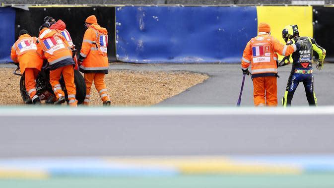 Pembalap Monster Energy Yamaha, Valentino Rossi, dibantu keluar arena usai terjatuh pada balapan MotoGP Prancis di Le Mans, Minggu (11/10/2020). Petrucci finis pertama dengan catatan waktu 45 menit 54,736 detik. (AP Photo/David Vincent)