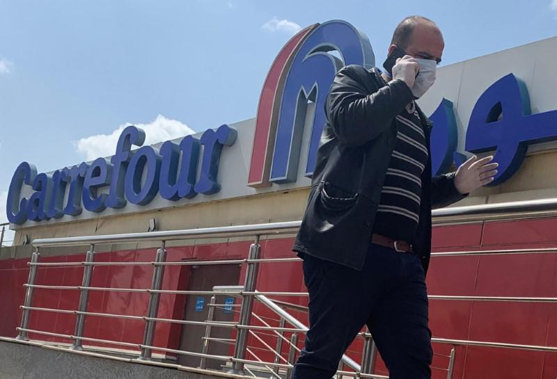 A man wearing a protective face mask walks outside a Carrefour hypermarket while Egypt ramps up its efforts to slow the spread the coronavirus disease (COVID-19) in Cairo