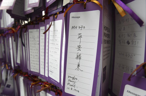 """A message card reading """"MH370 comes back safely"""" is tied up for passengers aboard a missing Malaysia Airlines plane, outside a shopping mall in Kuala Lumpur, Malaysia, Friday, March 14, 2014. A U.S. official said that the missing Malaysia Airlines flight MH370 pinged a satellite for four hours after it went missing, indicating that it may have stayed in the air long after its last contact with the ground. Malaysian authorities are widening their search westward, toward India, as a result. (AP Photo/Lai Seng Sin)"""