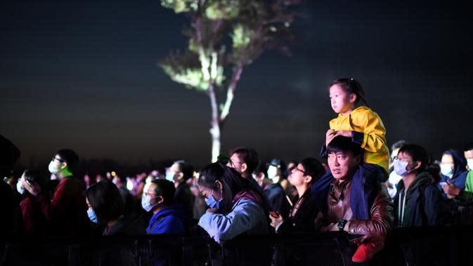 Seorang pria menggendong anaknya saat mereka menyaksikan Festival Musik Rye yang digelar selama dua hari di Beijing pada 18 Oktober 2020. (Photo by Noel Celis / AFP)