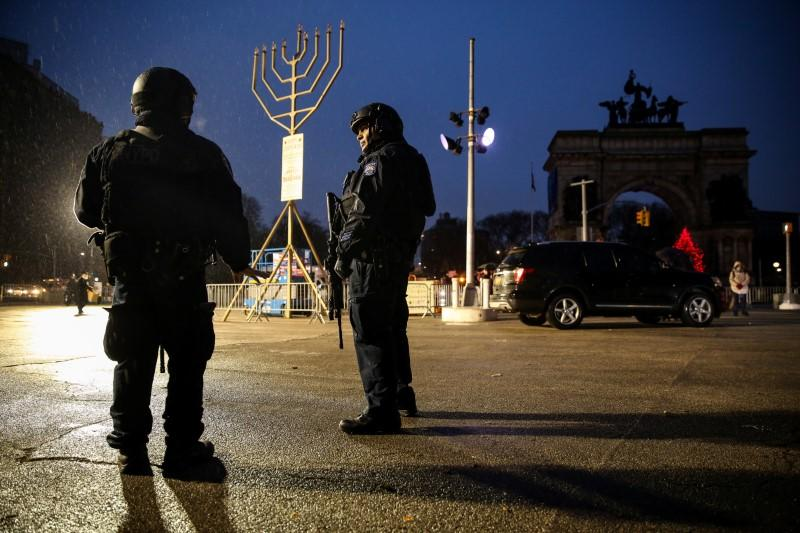 New York Police Department (NYPD) officers stand guard ahead of gathering at Grand Army Plaza in solidarity with the victims after an assailant stabbed five people attending a party at an Hasidic rabbi's home in Monsey, N.Y., on December 28, 2019, while th