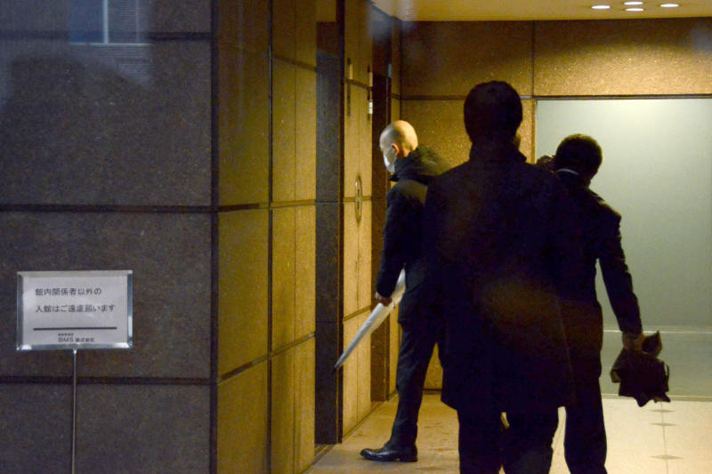 Tokyo prosecutors enter a building where the office of Junichiro Hironaka, a Japanese lawyer of former Nissan Chairman Carlos Ghosn, is located, in Tokyo Wednesday, Jan. 8, 2020. Prosecutors raided Hironaka's office where Ghosn had visited regularly before skipping bail last week and fleeing to Lebanon. Ghosn was under strict bail conditions while preparing for his trial on financial misconduct allegations. But he had been allowed to use a computer at his lawyer's office under those conditions.  (Kyodo News via AP)