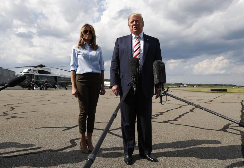 President Donald Trump, with first lady Melania Trump, speaks to the media before boarding Air Force One in Morristown, N.J., Sunday, Aug. 4, 2019. (AP Photo/Jacquelyn Martin)
