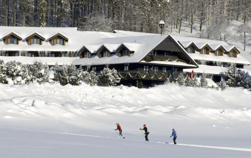 """FILE - This undated file photo provided by the Trapp Family Lodge shows cross-country skiers outside the lodge in Stowe, Vt. After a televised update of """"The Sound of Music"""" on Dec. 5, 2013, the hills of Vermont were alive with phones ringing at the lodge. Three-quarters of a century after the singing family arrived from Austria, they're still in demand at the 96-room chalet style inn they started. The family moved to the spot in 1942 after visiting Vermont on a singing tour and vacationing in Stowe. (AP Photo/Trapp Family Lodge, File)"""