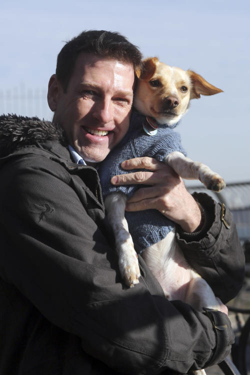 "In this Saturday, Jan. 19, 2013 photo, Michael Wright and his dog Toby pose for a portrait in New York. Toby, previously named Fumble, last year's Animal Planets' ""Puppy Bowl"" MVP winner, was adopted before the show aired. Wright said he found out about Fumble's participation toward the end of the adoption process, and plans to watch this year's show to catch any flashbacks of last year's MVP playing his heart out. (AP Photo/Mary Altaffer)"