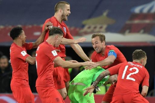 England's players mob goalkeeper Jordan Pickford after beating Colombia on penalties to reach the World Cup quarter-finals