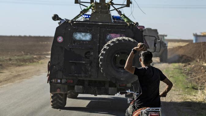 Seorang pria Kurdi menaiki motor melempar batu ke kendaraan militer Turki di dekat kota Al-Muabbadah, bagian timur laut Hassakah, Suriah (8/11/2019). Aksi dilakukan memprotes terhadap serangan militer yang dilancarkan Turki. (AFP/Delil Souleiman)