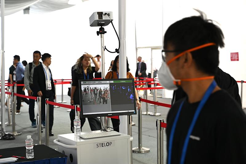 Visitors walk through temperature screening at the Singapore Airshow, amid fears over the spread of the COVID-19 coronavirus, in Singapore on February 13, 2020. (Photo by ROSLAN RAHMAN / AFP) (Photo by ROSLAN RAHMAN/AFP via Getty Images)