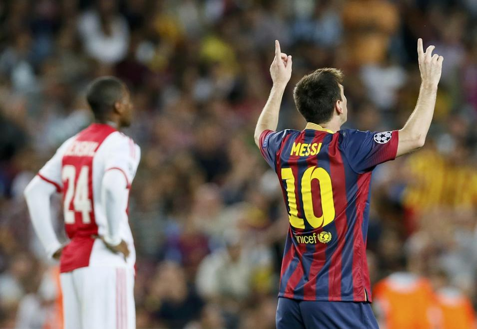 Barcelona's Messi celebrates scoring his second goal against Ajax as Ajax's Denswil reacts during their Champions League soccer match at Camp Nou stadium in Barcelona
