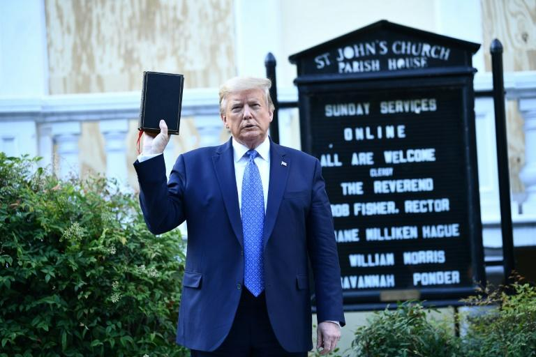 US President Donald Trump holds up a bible in front of St John's Episcopal Church after walking across Lafayette Park from the White House in Washington, DC on June 1