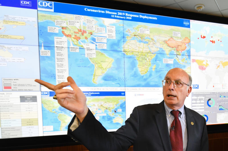 FILE - In this Feb. 13, 2020, file photo, Jay Butler, deputy director for infectious diseases at the Centers for Disease Control and Prevention (CDC), speaks to the media in regards to the novel coronavirus, while standing in front of a map marked with areas having reported cases, inside the Emergency Operations Center in Atlanta. In the United States, the nation with the most pandemic deaths, the reporting of vital coronavirus case and testing data is not keeping pace with its speedy spread. Public health officials nationwide lean too heavily on faxes, email and spreadsheets, sluggish and inefficient 20th-century tools. (AP Photo/John Amis, File)