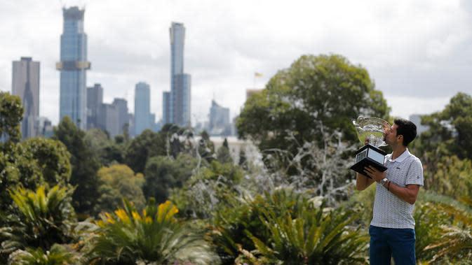 Petenis Serbia, Novak Djokovic mencium piala juara tunggal putra Australia Terbuka 2020 saat sesi pemotretan di Royal Botanic Gardens Victoria, Melbourne, Australia, Senin (3/2/2020). Djokovic sudah mengoleksi sebanyak 17 gelar grand slam dengan kemenangan kali ini. (AP Photo/Dita Alangkara)