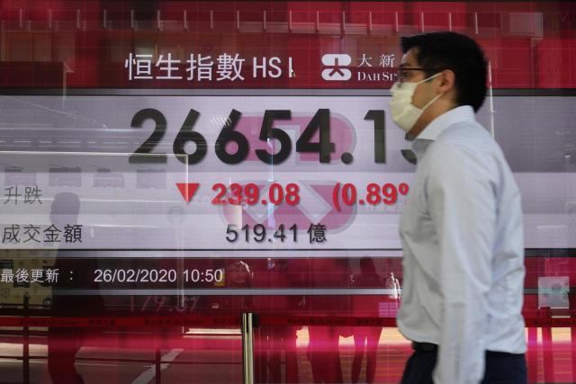 Un hombre camina delante de una pantalla que muestra la evolución de la bolsa de Hong Kong. (AP Photo/Vincent Yu)