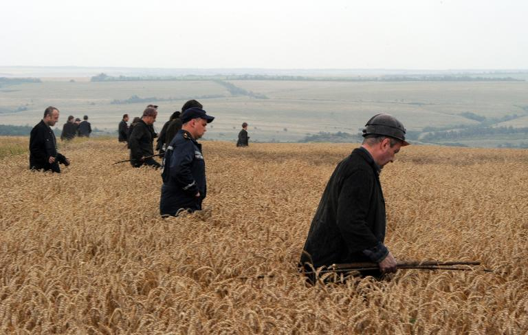 A group of Ukrainian miners assist in the search for bodies in a wheat field at the crash site of flight MH17, in rebel-held east Ukraine, on July 18, 2014