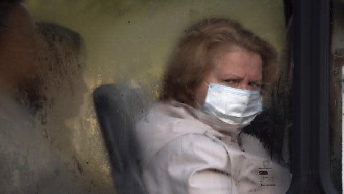 Seorang wanita yang memakai masker wajah untuk melindungi dari infeksi COVID-19 terlihat melalui jendela bus kota di St. Petersburg, Rusia, 28 September 2020. Kematian terbesar akibat COVID-19 dipimpin oleh Amerika Serikat, Brasil, dan India. (AP Photo/Dmitri Lovetsky)