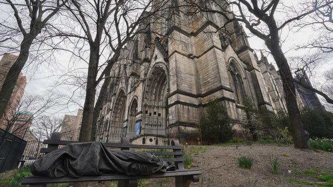 Patung orang yang tidur terlihat di bangku halaman Katedral St. John the Divine yang akan menjadi rumah sakit lapangan untuk menangani pasien virus corona (Covid-19) di New York, 7 April 2020. Saat ini New York menjadi negara bagian yang memiliki kasus corona tertinggi di AS. (Bryan R. Smith/AFP)