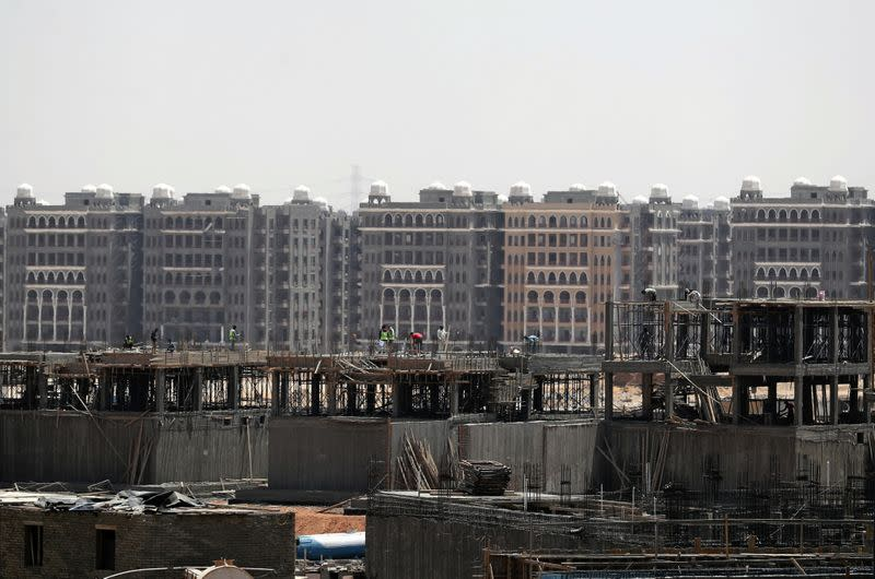 Workers stand on a building under construction in the New Administrative Capital (NAC), east of Cairo