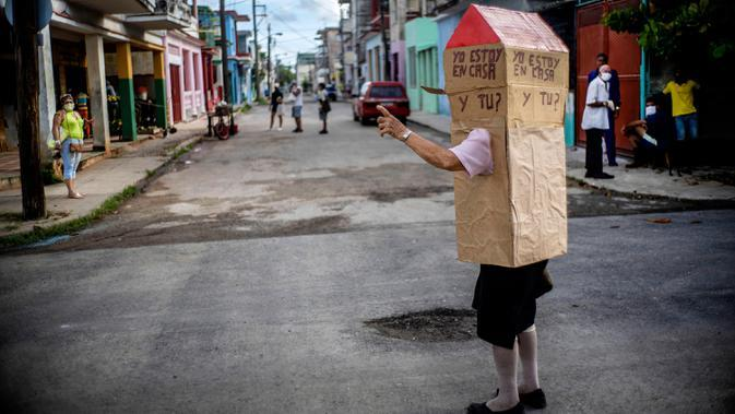 Pensiunan perawat, Feridia Rojas memakai kotak kardus berbentuk rumah untuk melindungi dirinya dari penyebaran Covid-19 di Havana, Kuba, 8 Juli 2020. Kardus pelindung pensiunan berusia 82 tahun itu dilengkapi pesan yang ditulis tangan dalam bahasa Spanyol