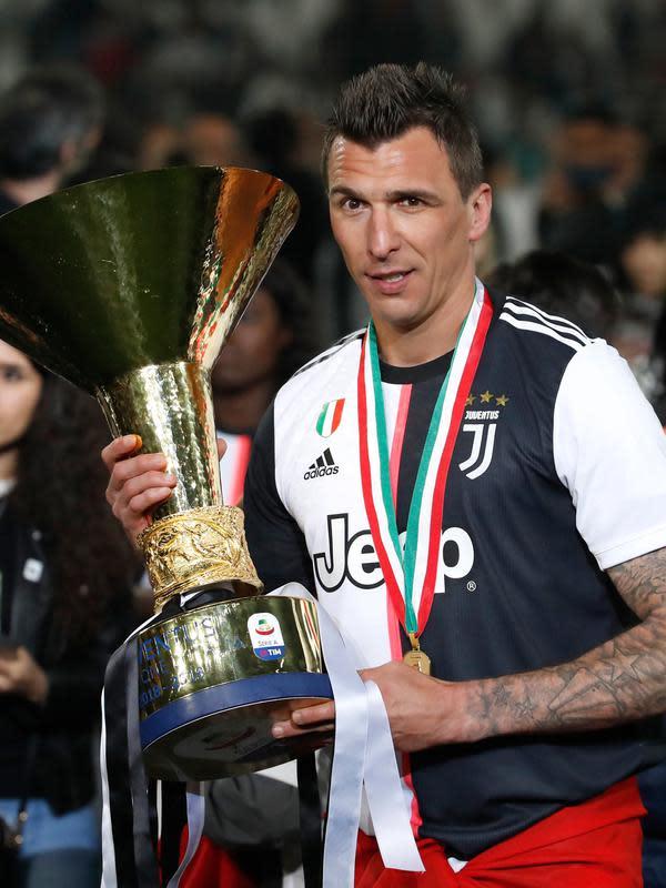 Striker Juventus, Mario Mandzukic berpose dengan Piala Liga Italia Serie A di Stadion Allianz, Turin (19/5/2019). Juventus berhasil meraih 97 angka dengan unggul 11 angka dari Napoli yang berada di peringkat kedua. (AP Photo/Antonio Calanni)