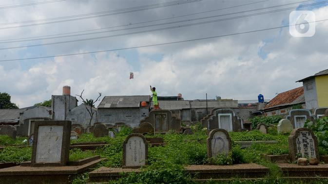 Anak-anak menerbangkan layang-layang di Tanah Makam Cipinang Besar Utara, Jakarta, Selasa (14/1/2020). Pemprov DKI Jakarta berencana terus menambah Ruang Publik Terpadu Ramah Anak (RPTRA) di sejumlah wilayah. (merdeka.com/Imam Buhori)