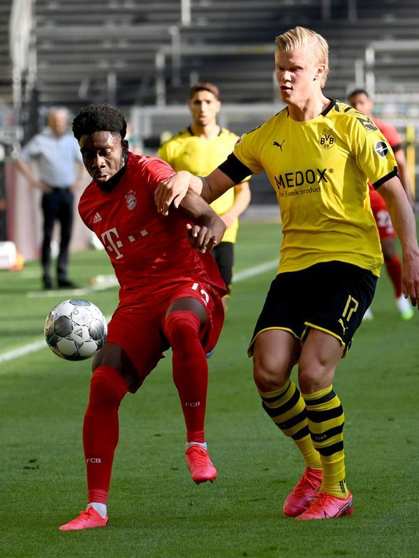 Bek Bayern Munchen, Alphonso Davies, mengawal ketat penyerang Borussia Dortmund, Erling Haaland, pada laga pekan ke-28 Bundesliga di Signal Iduna Park, Rabu (27/5/2020). (AFP/Federico Gambarini/POOL)