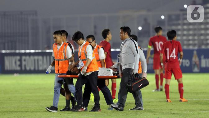 Pemain Timnas Indonesia U-19, M Supriadi ditandu keluar lapangan akibat cedera saat melawan Hong Kong pada laga kualifikasi Grup K Piala AFC U-19 2020 di Stadion Madya Gelora Bung Karno, Jakarta, Jumat (8/11/2019). Indonesia unggul 4-0. (Liputan6.com/Helmi Fithriansyah)