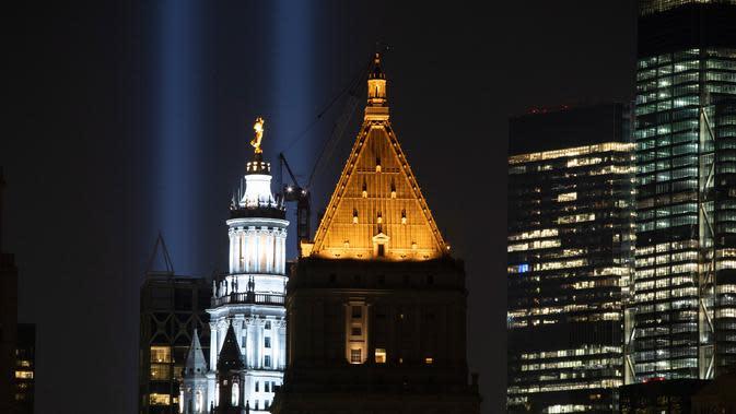 Instalasi cahaya bertajuk 'Tribute in Light' memperingati serangan gedung kembar menerangi langit di lower Manhattan, New York, Selasa (10/9/2019). Cahaya kembar itu jadi simbol menara kembar WTC yang hancur diserang kelompok pembajak pesawat 18 tahun silam. (AP/Mark Lennihan)