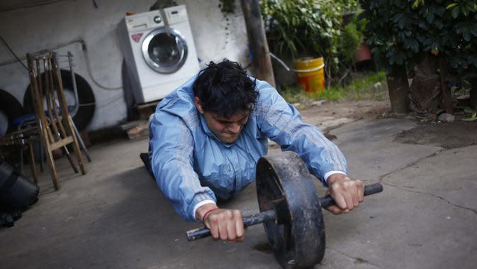 Yamil Peralta melakukan latihan di rumahnya di Jose C. Paz di pinggiran Buenos Aires, Argentina, 29 Juli 2020. Di tengah lockdown COVID-19, petinju Olimpiade dan profesional ini mendapat pekerjaan di perusahaan sampah untuk memenuhi kebutuhannya. (AP Photo/Marcos Brindicci)
