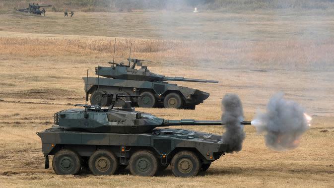 Tank Type 16 melepaskan tembakan saat ambil bagian dalam latihan Pasukan Bela Diri Darat Brigade Lintas Udara ke-1 di tempat pelatihan Narashino, Funabashi, Prefektur Chiba, Jepang, 12/1/2020). Latihan mensimulasikan pengusiran musuh yang mendarat di pulau-pulau terpencil. (Kazuhiro NOGI/AFP)