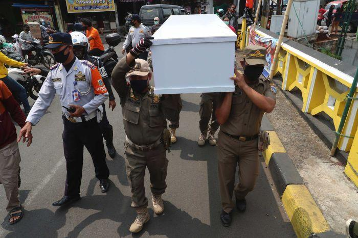 Indonesian officials carry a mock coffin as they walk around a busy intersection in Jakarta.