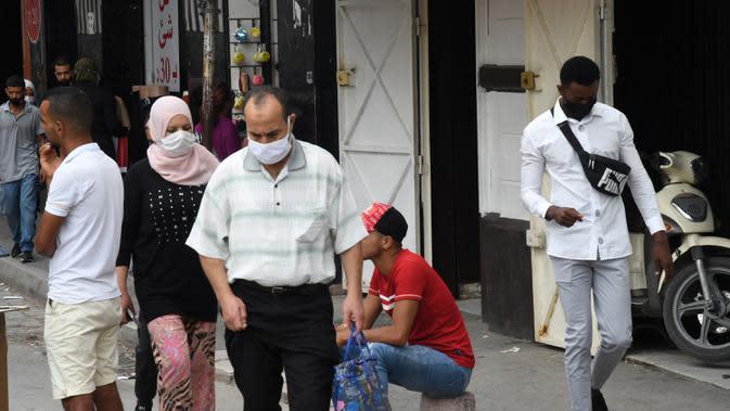 Orang-orang yang mengenakan masker berjalan di sebuah jalan di Tunis, Tunisia, pada 5 Oktober 2020. Perdana Menteri Tunisia Hichem Mechichi pada 3 Oktober mengumumkan serangkaian langkah untuk membatasi penyebaran cepat COVID-19 di negara tersebut. (Xinhua/Adel Ezzine)