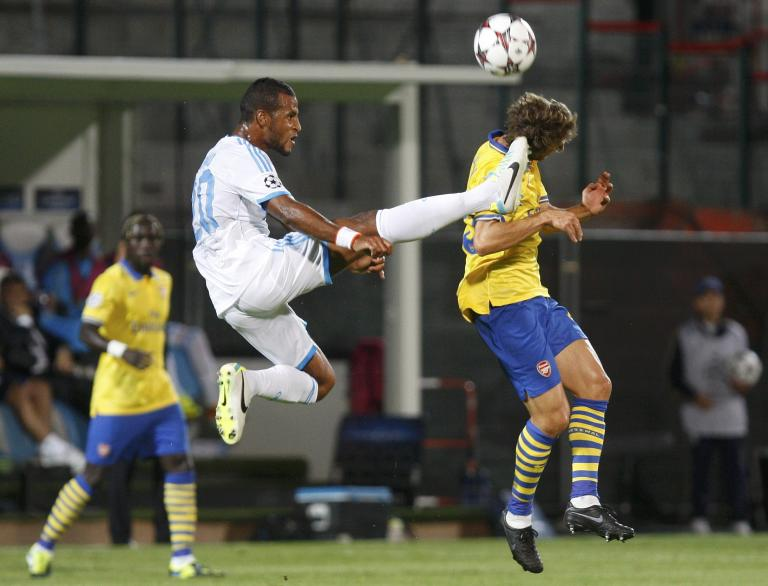 Arsenal's Flamini challenges Olympique Marseille's Romao during their Group F Champions League soccer match at the Velodrome stadium in Marseille