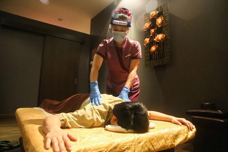 A therapist decked in protectice gear gives a demonstration of standard operating procedures that will be adhered to during a Thai massage at the Healthland Wellness Centre in Sunway Pyramid June 30, 2020. — Picture by Choo Choy May