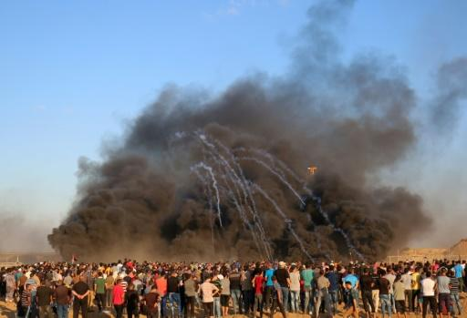 Palestinian protesters watch as tear gas canisters fired by Israeli forces comes through the black smoke of burning tyres during a demonstration on the Israeli border east of Gaza City on September 14, 2018