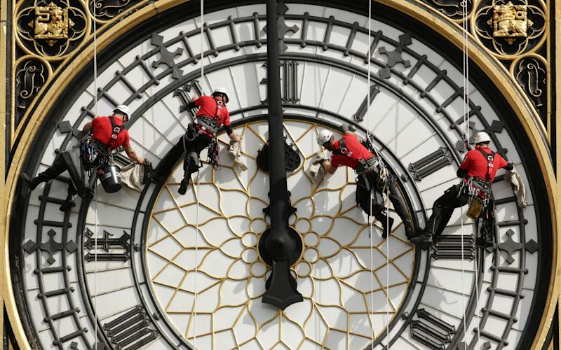 A specialist technical abseil team clean and inspect one of the four faces of the Great Clock last month - PA
