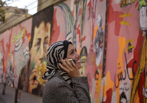 "In this Tuesday, Dec. 10, 2013 photo, Egyptian rapper Myam Mahmoud speaks with a friend on her phone while looking at political graffiti in downtown Cairo. Mahmoud, an 18-year-old Egyptian, rapped her way to the semi-finals of the Middle East's hit TV show ""Arabs Got Talent."" While she didn't win the program, Mahmoud did succeed in throwing a spotlight on something more than just herself. On a very public stage, her songs pulled back the curtain on the slew of challenges that women across the Arab world are fighting to overcome. ""I wanted to tell girls in Egypt and everywhere else that they are not alone, we all have the same problems, but we cannot stay silent, we have to speak up,"" Mahmoud told The Associated Press during an interview at her home. (AP Photo/Maya Alleruzzo)"