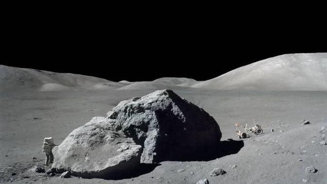 Pada 13 Desember 1972, astronaut ilmuwan NASA, Harrison Schmitt, berdiri di sebelah batu besar selama misi Apollo 17. Mosaik ini dibuat dari dua foto yang diambil oleh sesama penjelajah Bulan, Eugene Cernan. (NASA)