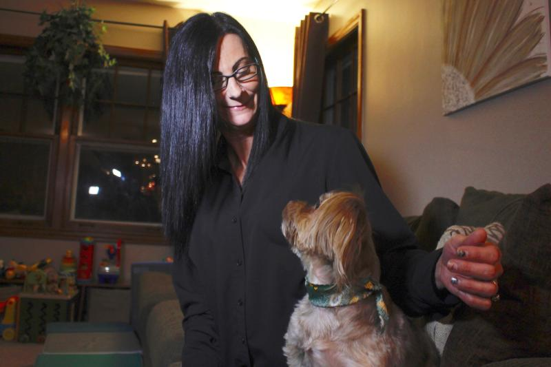 In this Nov. 5, 2019 photo, Amy Carter looks at her dog Bentley at her home in St. Francis, Wis. Carter gives him CBD, which she says has reduced his epilepsy-related seizures. The federal government has yet to establish standards for CBD that will help pet owners know whether it works and how much to give. But the lack of regulation has not stopped some from buying it, fueling a $400 million CBD market for pets that grew more than tenfold since last year and is expected to reach $1.7 billion by 2023, according to the cannabis research firm Brightfield Group. (AP Photo/Carrie Antlfinger)