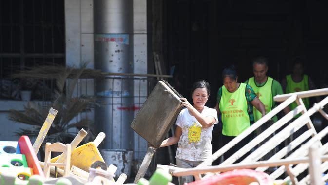 Para sukarelawan membersihkan sebuah sekolah dasar di Guojiatuo di Distrik Jiangbei, Chongqing, China barat daya (23/8/2020). Upaya bantuan bencana dilakukan di Chongqing setelah air banjir surut. (Xinhua/Wang Quanchao)