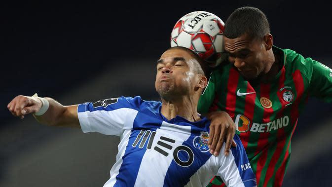 Bek FC Porto, Pepe, berebut bola dengan gelandang Maritimo, Moreno, pada laga lanjutan Liga Portugal di Dragao Stadium, Porto, Kamis (10/6/2020) waktu setempat. Porto menang tipis 1-0 atas Maritimo. (AFP/Jose Coelho/Pool)