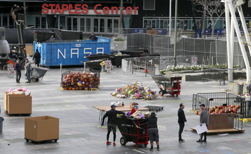 Workers remove thousands of items left in honor of Kobe Bryant, including hundreds of basketballs, from X-Box Plaza across Chick Hearn Court from Staples Center, home of the Los Angeles Lakers, early Monday, Feb. 3, 2020, in Los Angeles. Mourners left the items after the death of the former Lakers legend, his daughter and seven others, in a helicopter crash one week ago. (AP Photo/Reed Saxon)