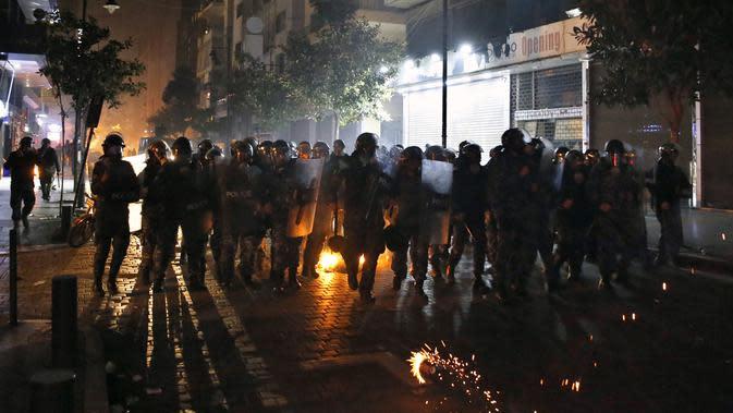 Polisi antihuru-hara berlari ke arah demonstran antipemerintah saat protes menentang elite penguasa di Beirut, Lebanon, Selasa (14/1/2020). Demonstran menganggap elite penguasa gagal mengatasi ekonomi yang menurun tajam. (AP Photo/Bilal Hussein)