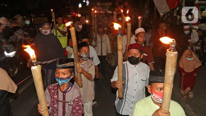 Sejumlah warga saat melakukan pawai obor di Kawasan Rempoa, Tangerang Selatan, Rabu (19/08/2020). Pawai obor tersebut dilakukan dalam rangka menyambut peringatan tahun baru Islam 1 Muharram 1442 H. (Liputan6.com/Herman Zakharia)