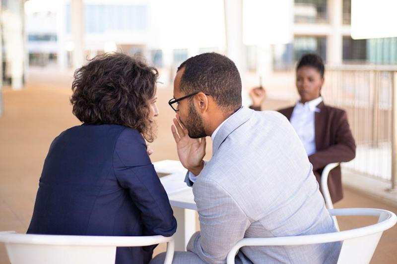 employees gossiping about young female colleague by whispering to each other